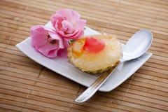 Fruchtkuchen auf einer Platte nahe bei einer Rose Stockbild