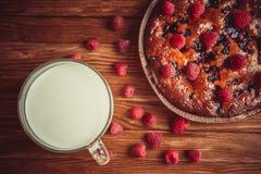 Fruchtkuchen und Schale Milch auf dem Tisch Lizenzfreie Stockbilder