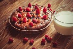 Fruchtkuchen und Schale Milch auf dem Tisch Lizenzfreies Stockfoto