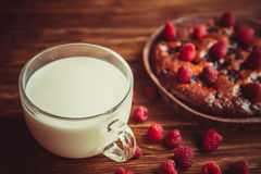 Fruchtkuchen und Schale Milch auf dem Tisch Lizenzfreie Stockfotografie
