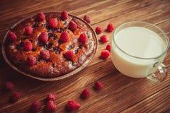 Fruchtkuchen und Schale Milch auf dem Tisch Stockbild