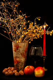 Fruchtmischung, Glas Wein, rote Kerze und Vase Blumen auf schwarzem Hintergrund Stockfoto