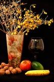 Fruchtmischung, Glas Wein und Vase Blumen auf schwarzem Hintergrund Stockbilder
