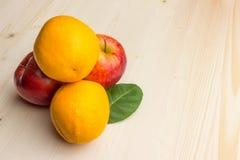 Fruchtorangen und -äpfel auf einem hellen hölzernen Hintergrund Stockfoto