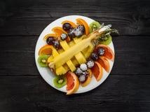 Fruchtplatte auf einem dunklen hölzernen Hintergrund Stockbild
