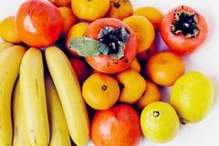 Fruchtplatte auf weißem Hintergrund Mandarinen, Bananen, Persimonen und Zitronen stockfoto