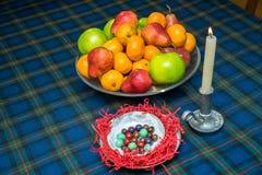 Fruchtplatte, -nuzelnuts und -kerze Stockfotos