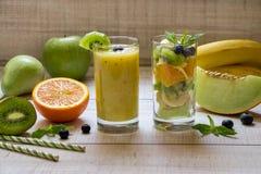 Fruchtsmootie und -salat in 2 Gläsern stockfotos