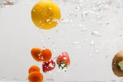 Fruchtspritzen in Wasser stockfotos