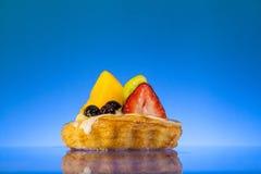 Fruchttörtchen im blauen Hintergrund Stockbild