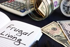 Frugal living written on a note pad. Frugal living written on a note pad and money royalty free stock photo