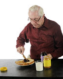 Frugal Senior. A senior man making himself a peanut butter and jelly sandwich on whole grain bread stock photo