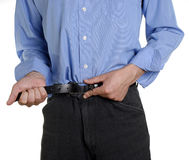 Frugal times. Conceptual shot of business man tightening his belt during tough economic times royalty free stock photography