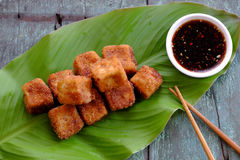 Vegetarian food, fried tofu. Frugal vegetarian food from Vietnamese cuisine, fried tofu with spice power, cover with crispy flour, homemade food on green leaf stock photo