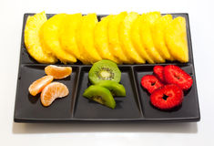 Fruit. Sliced of ananas, kiwi, mandarin and strawberries on a black saucer Stock Photography