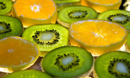 Fruit. Sliced kiwis and mandarins with lights coming from behind them royalty free stock images
