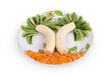 Fruit. Bananas of a kiwi and tangerine on a plate a white background Royalty Free Stock Photos