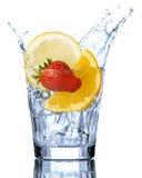 Fruit. Splashing orange, lemon and strawberry into a water glass Stock Photos