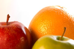 Fruit against white background. Composition with red and green apples plus orange Stock Photos