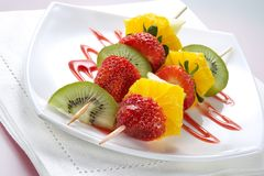 Fruit allsorts on skewers. Served atop of a plate decorated by strawberry jam Royalty Free Stock Image
