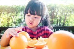 Free Fruit And Vegetable For Kids Concept. Little Cute 3-4 Years Old Girl With Sliced Orange On Wooden Plate Royalty Free Stock Photos - 153102038