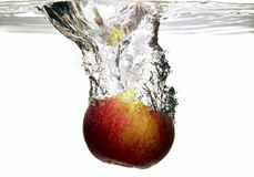 Fruit apple is dropped into water Royalty Free Stock Images
