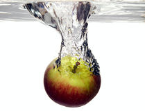 Fruit apple is dropped into water stock photography