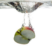Fruit apple is dropped into water. Cut red fruit apple is dropped into water Stock Image