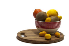 Fruit arrangement in the bowl and on the kitchen board Royalty Free Stock Image