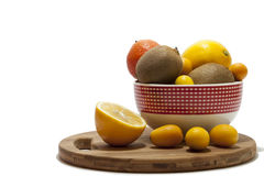 Fruit arrangement in the bowl and on the kitchen board Stock Photos