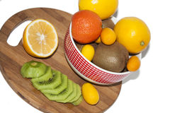 Fruit arrangement in the bowl and on the kitchen board Royalty Free Stock Images