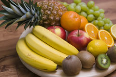 Fruit background. Colourful composition arranged on wooden chopping board, consisting of fresh fruit. The ingredients are: pineapple, bananas, kiwis, grapes Stock Photo