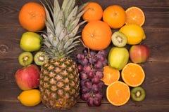 Fruit background with orange, kiwi, grape, apples and lemon on the wooden table stock photos