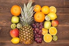 Fruit background with orange, kiwi, grape, apples and lemon on the wooden table royalty free stock photo