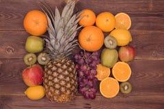Fruit background with orange, kiwi, grape, apples and lemon on the wooden table royalty free stock image