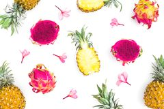 Fruit background of pineapple and dragon fruits with tropical pink flowers on white background. Flat lay, top view. Stock Photos