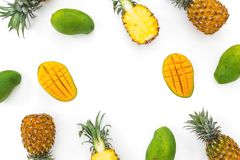 Fruit background of pineapple and mango fruits on white background. Flat lay, top view. Tropical concept. Stock Image