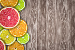 Fruit background with slices of orange, grapefruit, lemon and lime on wooden desk. Royalty Free Stock Photos