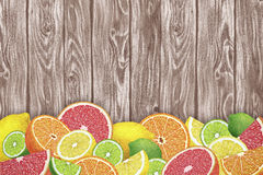 Fruit background with slices of orange, grapefruit, lemon and lime on wooden desk. Stock Photos