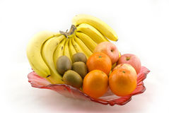 Fruit. Bananas, apples, oranges and kiwies on a red petal shape fruit dish Royalty Free Stock Photos