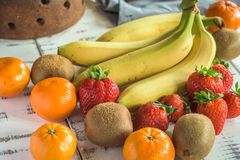 Fruit. Bananas,Strawberries,kiwis and tangerines on a white wooden background royalty free stock photography