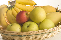 Fruit basket. Consists of bananas, pear, apple and mangoes, mainly yellow color except for the apple Stock Photos
