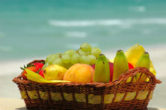 Fruit basket. With bananas, peaches and grapes. Tropical coastline in background Royalty Free Stock Image