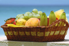 Fruit basket. Basket with fruits on the tropical sea background Royalty Free Stock Images