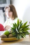 Fruit Basket. A fruit basket laying on the kitchen table, with kiwi,pineapples and limes Royalty Free Stock Photos