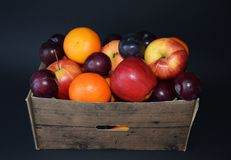 Fruit basket with apple, orangen and plum. Healthy fruits in cartoon basket. Apple, orangen and plum against a black background Royalty Free Stock Images