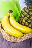 Fruit basket with bananas and ananas Royalty Free Stock Images