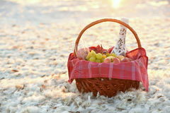 A fruit basket and champagne among white feathers on the lake Royalty Free Stock Images