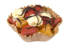 Fruit basket with chocolate sauce. Waffle fruit basket filled with strawberries, satsumas and ice cream drizzled with chocolate sauce Stock Image
