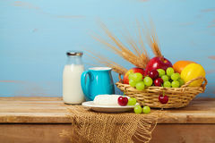 Fruit basket and dairy products on wooden table. Jewish holiday Shavuot background Stock Photo